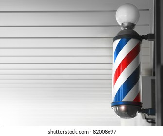 Old fashioned vintage barber shop pole against modern background
