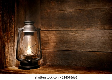 Old fashioned vintage kerosene oil lantern lamp burning with a soft glow light in an antique rustic country barn with aged wood wall and weathered wooden floor