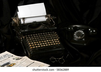 Old fashioned, vintage photo of an old type writer with phone , glasses and newspaper