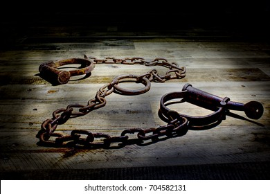 Old fashioned, vintage shackles on a rustic wooden background. The picture is reflective of incarceration, jail, kink, bound, rust, corrosion, cuffs, vintage, law enforcement, antiques