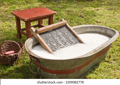 An old fashioned washing trougth filled with water, a vintage washboard and soap that wash the laundry
