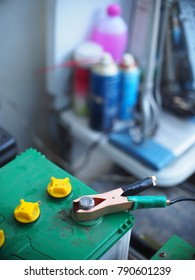 old fashioned wet cell acid lead dead 12 volts automotive vehicle car battery during recharge procedure crop closeup focus at a clamp on battery terminal selective focus blur background