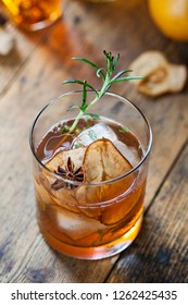 Old fashioned, whiskey drink with rosemary ice cubes and dry pear slice