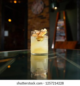 Old fashioned white cocktail with peach slices and cinnamon on glass restaurant table.