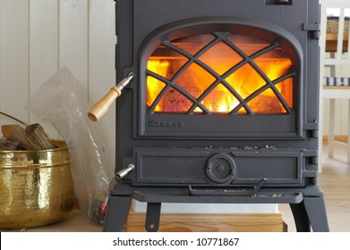 An old fashioned wood burning stove with a roaring fire.