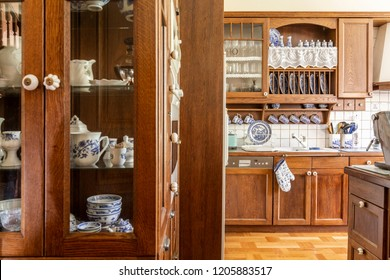 Old fashioned wooden cabinets with white and cobalt blue china in kitchen interior.