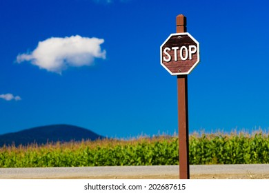 Old fashioned wooden stop sign against a blue sky, Stowe Vermont, USA