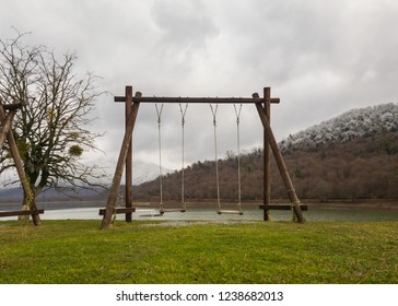 Old fashioned wooden swing at Kavreli Lake Gerogia with snow capped mountains in the background