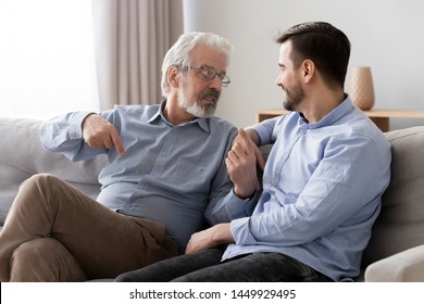 Old father wearing glasses talking with son, having pleasant conversation at home, mature dad and young man or grandson sitting on couch, discussing, sharing thoughts, family spending time together