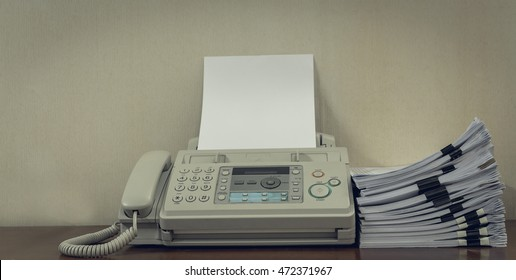 old fax machine on the table and stack of paper.
