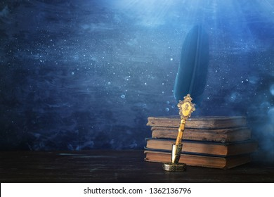 Old feather quill ink pen with inkwell and old books over wooden desk in front of black wall background. Conceptual photo on history, fantasy, education and literature topic