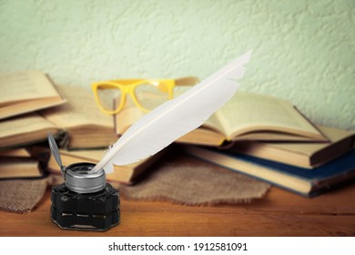 Old feather quill ink pen with inkwell and old books on wooden desk