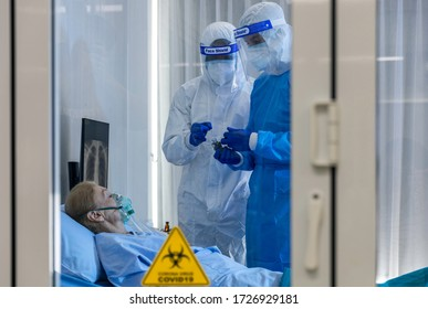 Old female Caucasian patient infected with virus under oxygen saturation treatment. Medical staff in PPE observe for urgent measure responding to respiratory failure in protective quarantine ward room