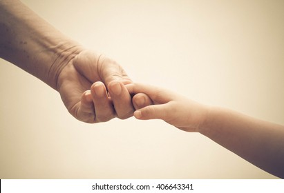 Old female hand holding young baby hand in vintage tone
