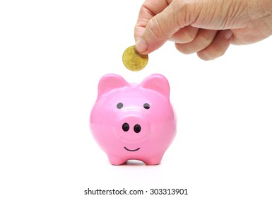 old female hand putting golden coins into pink piggy bank - saving money for retirement concept