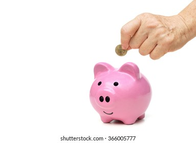 old female hand putting a golden coin into a pink piggy bank - saving for retirement concept