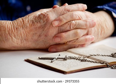 Old female hands with a cross and book