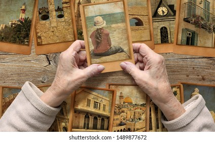 Old female hands hold old photo. Vintage photo cards background. Remembering Israel. Memory, life and dreams concept
