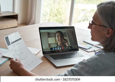 Old female hr reading cv during online job interview by video call. Senior employer checking indian seeker resume talking by social distance remote recruitment chat meeting videoconference on laptop.