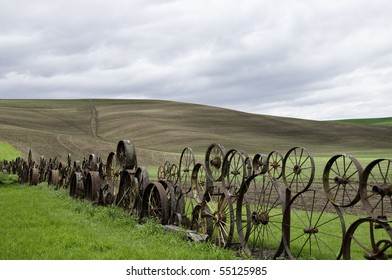 Old fence made of metal wheels.Rolling hill in background.
