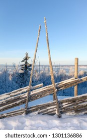 Old fence in Sweden with a view over snowy landscape of Dalarna