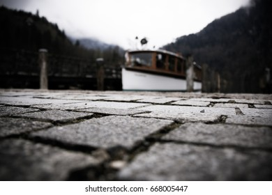 old ferry boat at the königssee in bavaria with the famous lake and the alps in the background and cobblestone in the unfocused front