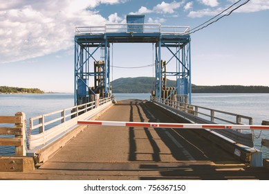 Old ferry dock and wooden pier located in the San Juan islands in the Pacific Northwest outside of Seattle, Washington. Islands, water and a cloudy sky are visible on this sunny day.