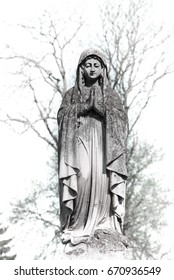 The old figure of the Virgin Mary, who prays in a cemetery (black and white concept)