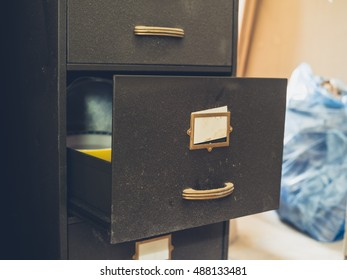 An old filing cabinet with an open drawer