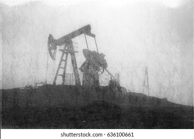 An old film black-and-white image of oil production in America USA. pumps rocking at dawn amid the damaged ecology of alpine meadows work to produce the energy of the modern world