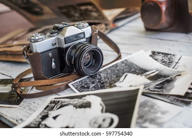 An old film camera and family album on a white wooden background among vintage families photos