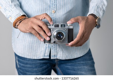 Old film camera in man's hand. Photography and hobby concept.