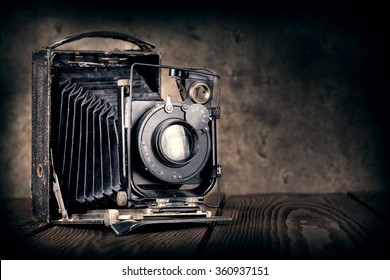 Old film camera on a wooden background