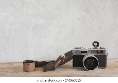 Old film camera and a roll of film on wood