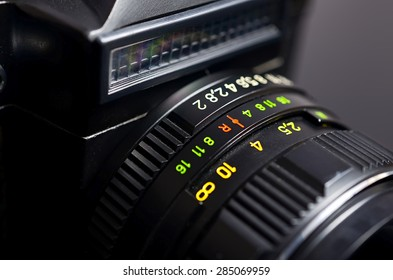 Old film DSLR camera with lens. The scale of the aperture, depth of field and distance. Close up view. Macro. Selective focus.