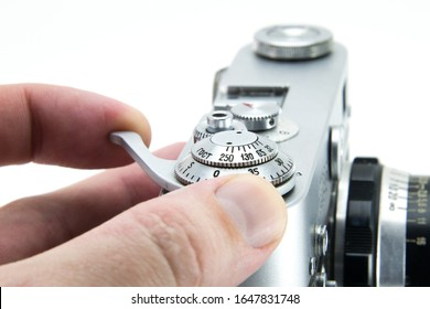 Old film retro camera. Human fingers cock the shutter and trigger. Using the camera with hands, shooting close-up. Metallic black. White isolated background.