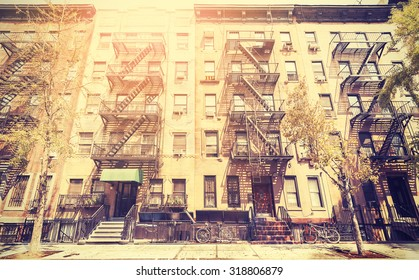 Old film retro style photo of New York building with fire escape ladders, USA.