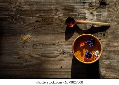 Old Finnish Sauna SPA Concept, wooden pot with water, flowers and a bucket, a kettle with hot water and a massage snag, on old wooden rustic sauna boards, top view, copy space