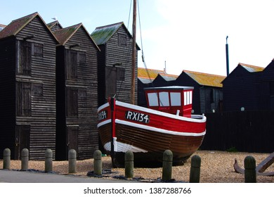 Old fisher boat on the beach of Hastings. Old fisher huts in the background. Towers to dry the nets.