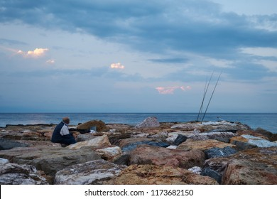 Old fisherman on the pier by the sea looking at his rods, waiting for the fish to bite early in the morning
