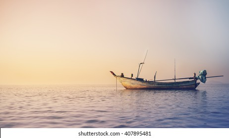 Old fisherman ship float on the sea, in sunrise