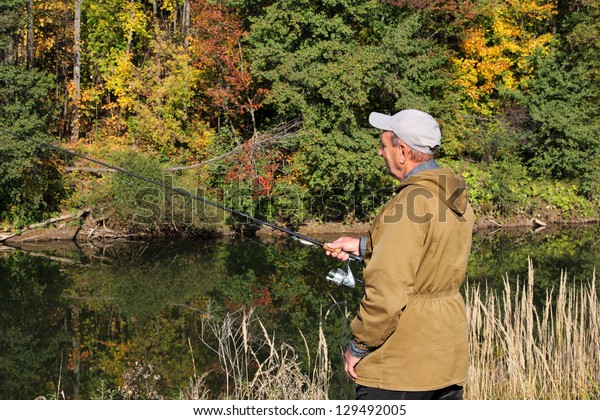 old fisherman with spinning on autumn river