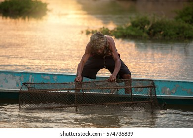 Old fisherman are working on the boat in mekong river sunset time.