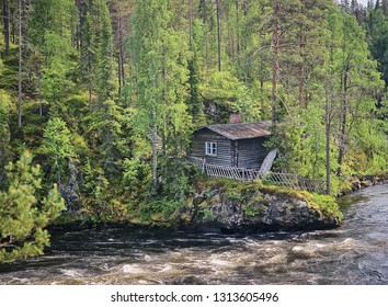 Old fisherman's hut along the Oulankajoki river at the Oulanka National Park in Kuusamo, Finland. Scenic view of the northern nature and the flowing water in the stream.