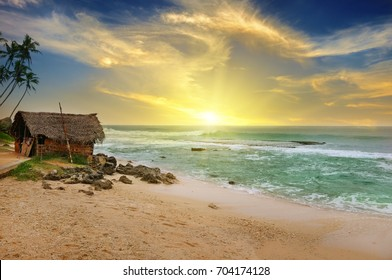 An old fisherman's hut on the shore of a picturesque ocean and a beautiful sunset on a cloudy sky.