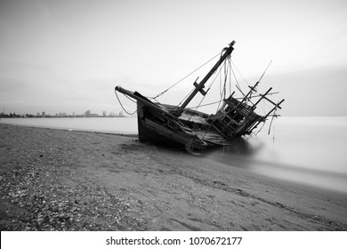 The old fishermen ruined small fishing boat going to be aground on the beach put a ship out of commission on sunset sky.