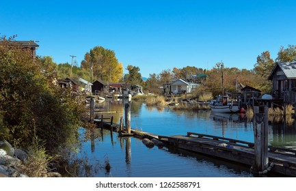 An old fishermen village located in the slough of river. Old houses with moorings and boats near the shore. Early autumn, old grass and yellow trees against the blue sky.