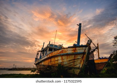 Old fishing boat on sunset sky background