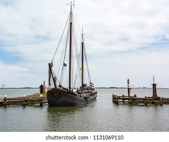 Old fishing boat sails into the harbor of Volendam (Netherlands)
