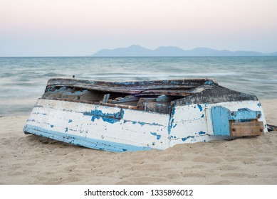An old fishing boat turned uopside down on a lake malawi beach in monkey bay.